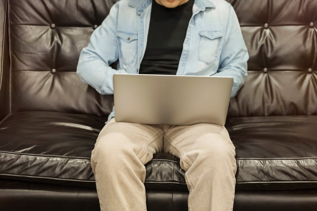 man sitting in a sofa while using his laptop